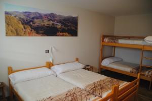 Vista de la cama doble y literas en la suite Gorosti. Double bed and bunk beds view in the 6pax arrangement of Suite Gorosti.
